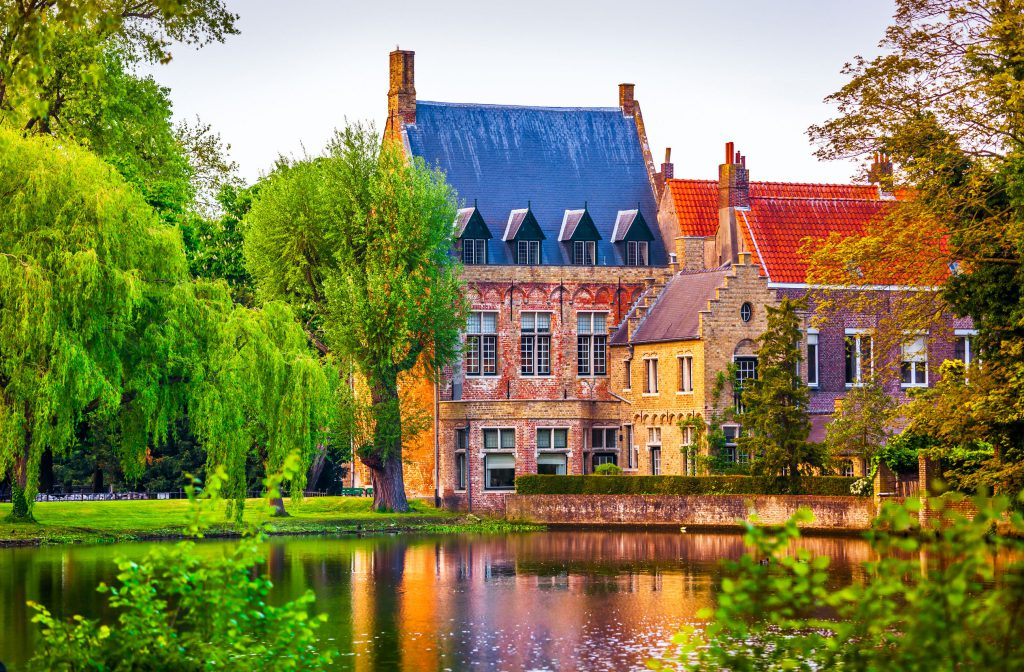 78996885 - vintage building over lake of love in minnewater park in bruges belgium near beguinage monastery of beguines. picturesque landscape with green trees sunset time.