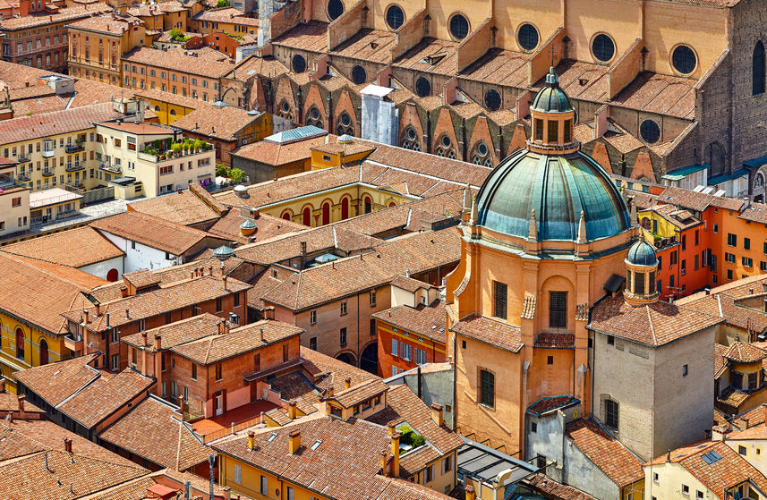 96975572 - bologna, italy. top view to dome of medieval ancient cathedral sanctuary of santa maria della vita. terracotta houses with tiled roofs. sunny day.