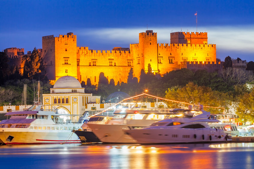 34306769 - mandraki harbour rhodes greece and the palace of the grand master of the knights of rhodes at night.