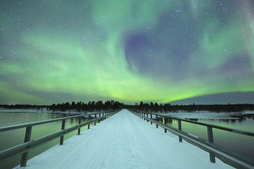 Spectacular aurora borealis (northern lights) over a bridge and a river in a snowy winter landscape in Finnish Lapland.